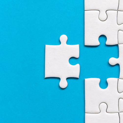 White jigsaw puzzle on blue background. Team business success partnership or teamwork