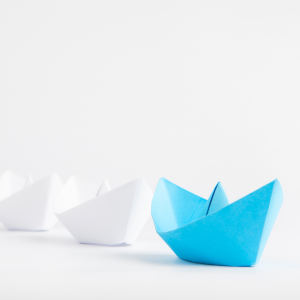 Leadership concepts with blue paper ship leading among white